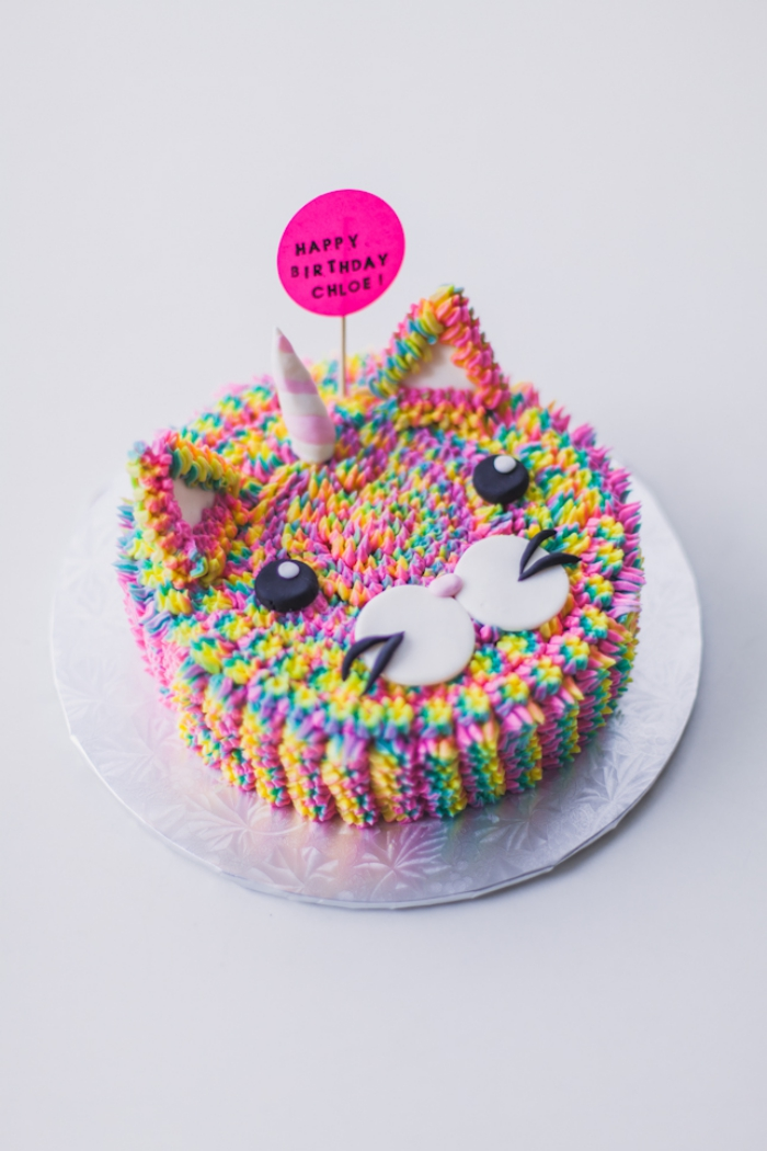 gâteau arc en ciel en forme de tête de matou, décoré de petites fleurs multicolore en glaçage