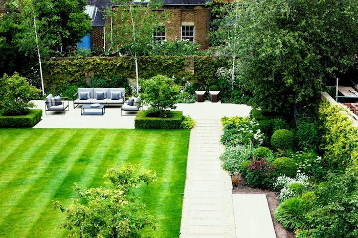 gazon vert et coin terrasse exterieur avec salon de jardin de meubles en métal avec coussin d assise bleu gris, mur de pierres envahi par lierre, buis, et arbres