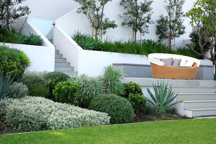 exemple de gazon vert, avec bordure d arbustes et autres végétaux bas, terrasse en pente avec canapé en rotin décoré de coussins gris et blancs