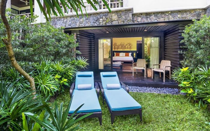 exemple de déco terrasse en gazon ver avec chaise longues en rotin avec matelas bleu, gazon vert et bordure de végétation tropicale