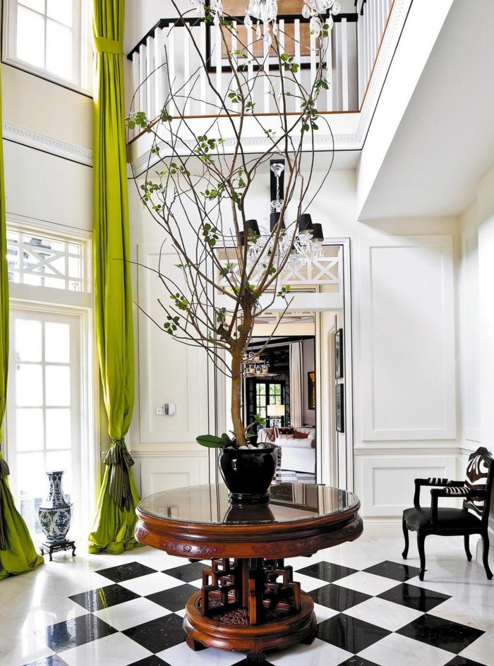 entrée blanche, grande fenêtre et rideaux verts, petite table ronde avec un arbre décoratif, carrelage damier, chaise baroque