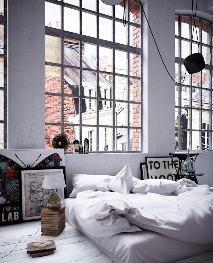 décoration de loft industriel avec de grandes fenêtres, linge de lit blanc sur un matelas blanc, parquet clair, deco artistique