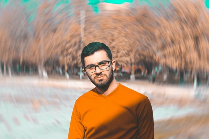 lunette de vue tendance, lunette hipster, grosse lunette de vue, homme brun avec une monture noire, pull au col en V en orange aux manches longues