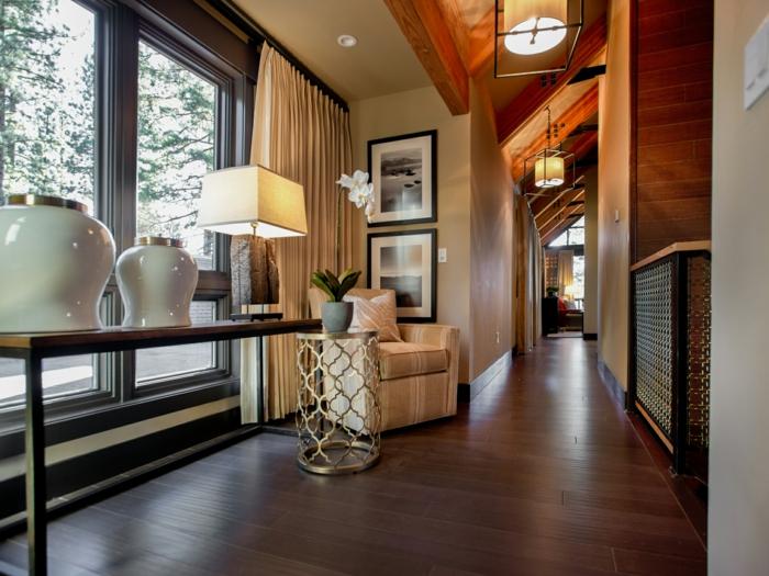 peintures encadrées, console en bois, sol boisé et fauteuil beige, plafond sous pente