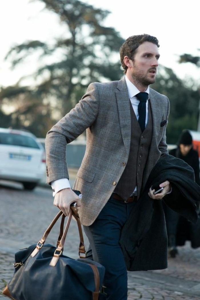 style gentleman, vetement homme stylé, vêtement homme classe, veste a carreaux gris et noir, pantalon bleu marine, grand sac de voyage en bleu marine, gilet marron, cravate noire
