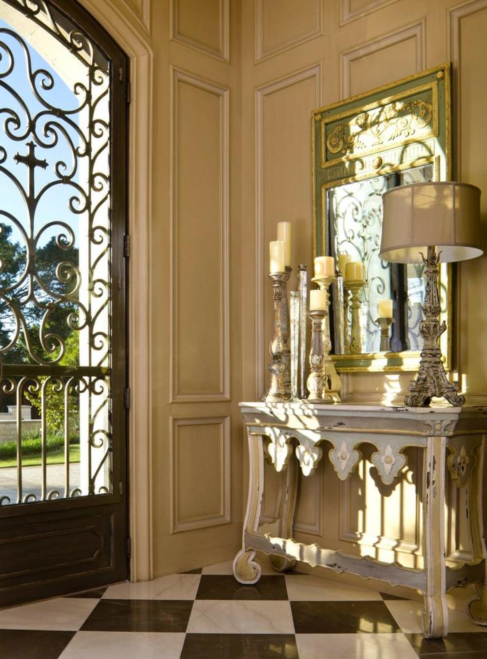 comment décorer l'entrée d'une grande maison, idée déco entrée maison chic avec un grand miroir, lampe abat-jour, bougeoirs couleur métallique
