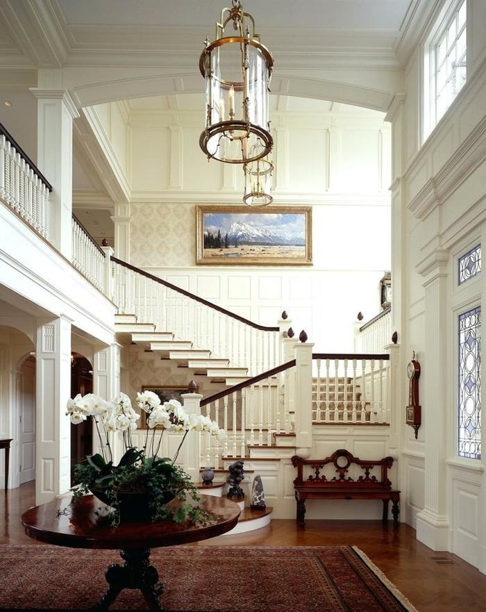 maison de luxe avec une décoration blanche et jolie architecture, petite banquette en bois sculpté, luminaires lanternes, table ronde en bois laqué