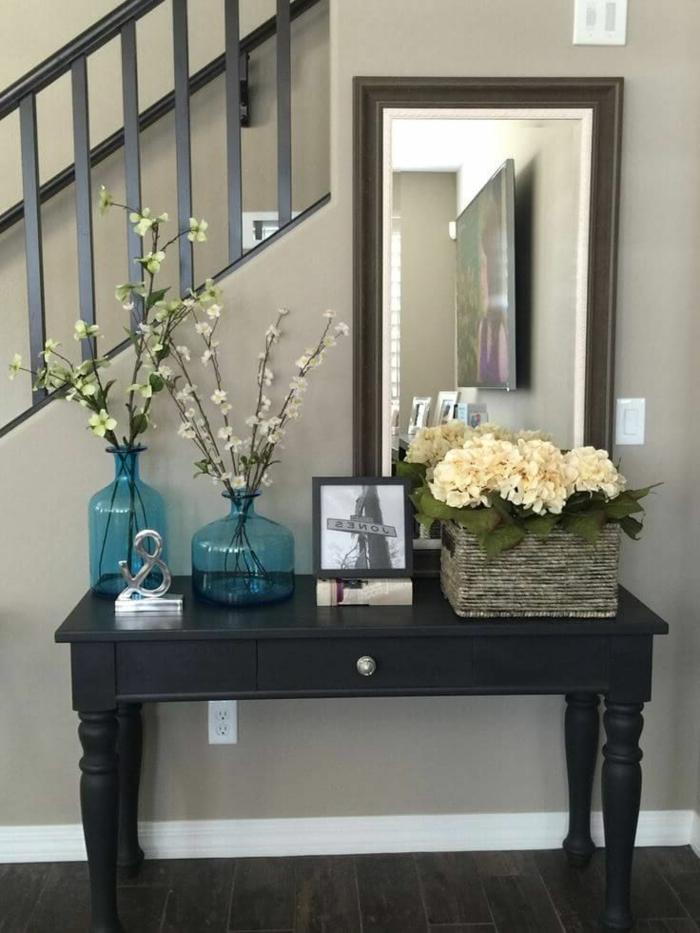 miroir rectangulaire, vases turquoises avec des tiges fleuries, bureau noir, panier rustique
