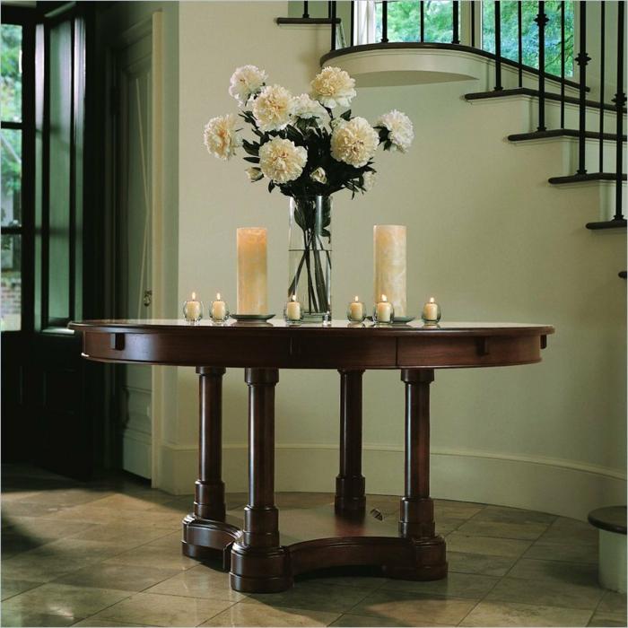 entrée simple et stylée, table en bois, bougies blanches, bouquet de pivoines près d'un escalier élégant