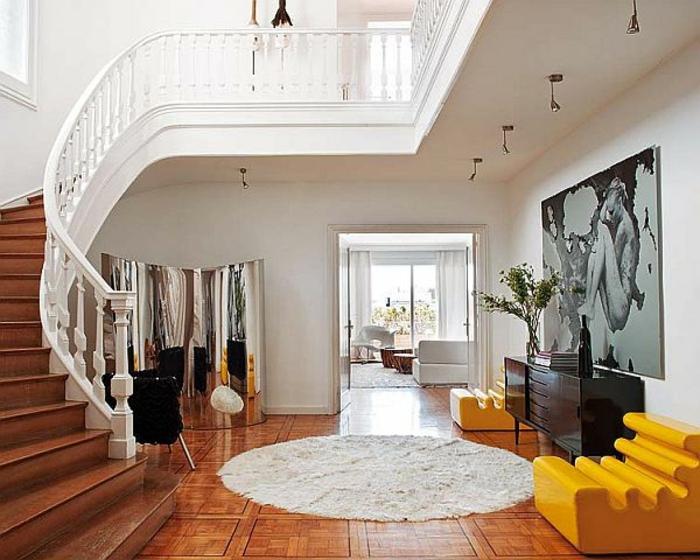 tapis rond, sol marron, escalier tournant, fauteuils jaunes, commode noire, peinture artistique géante
