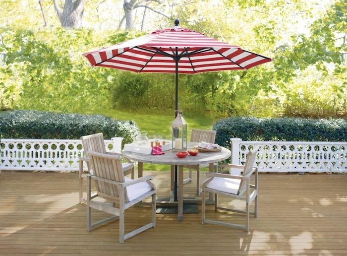 décoration terrasse en bois avec table et chaises bois brut et parasol rouge et blanc, gazon vert bordé de buis verts