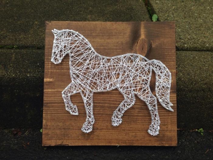 jolie déco murale DIY fait avec une planche de bois foncé et un fil blanc enrouler autour de clous en forme de cheval