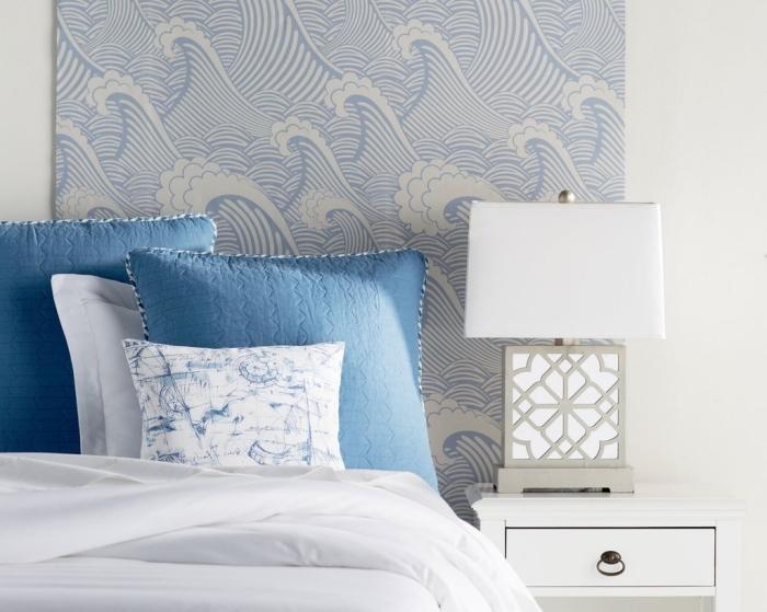 une bonne idée déco pour l'aménagement petit budget de la chambre parentale, une tête de lit en papier peint marinier à motif vagues qui s'accorde parfaitement avec la parure de lit