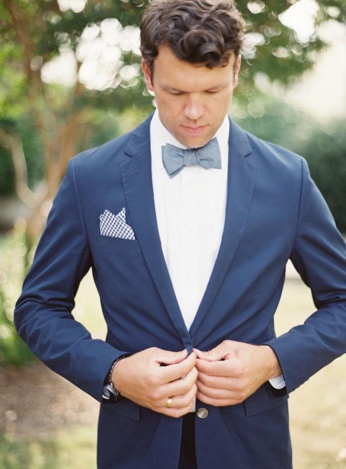 un costume bleu marine noeud papillon bleu gris pour une silhouette élégante et chic, un mouchoir à pois pour une touche d'originalité
