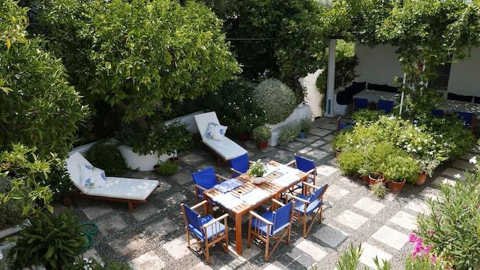 dalles de béton et gravier sur une terrasse exterieure moderne, chaises longues, table et chaises en bois, plantes en pots et arbres en mordure