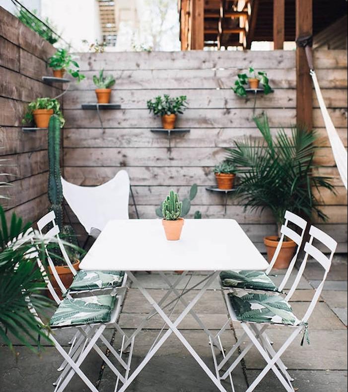 amenagement terrasse exterieure beton avec coin repas en table et chaises métalliques, clôture bois avec rangements pots de fleurs intégrées