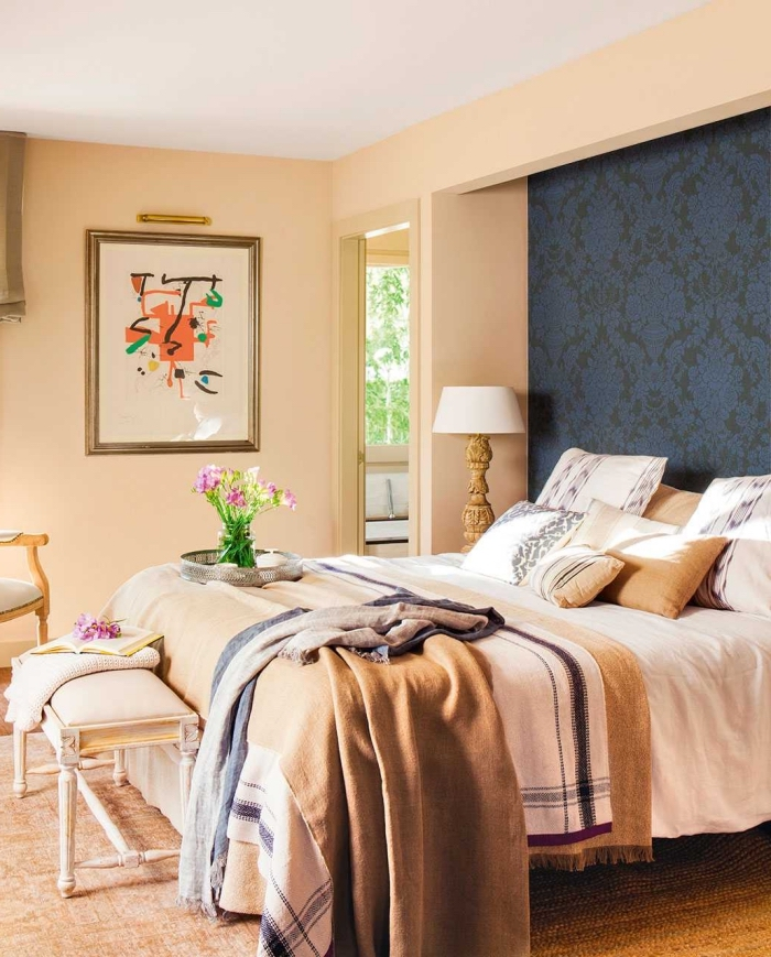 une niche murale derrière le lit tapissée de papier peint vintage qui fait office de tete de lit diy originale