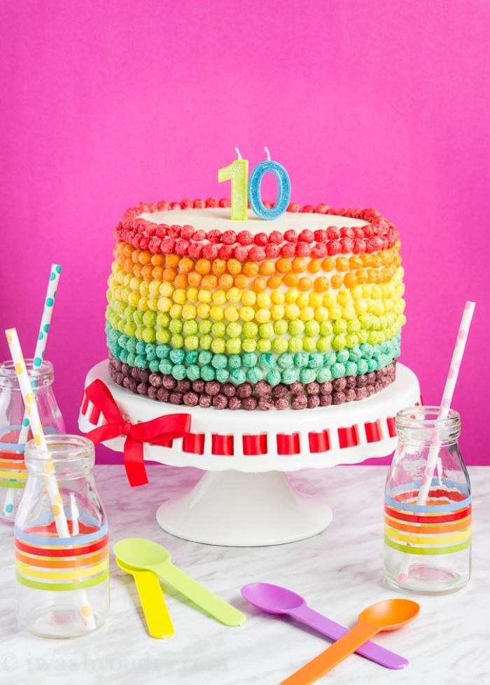 recette de gateau multicolore surprise avec des bonbons à la gelée à l'intérieure et une décoration de céréales colorées sur les côtés