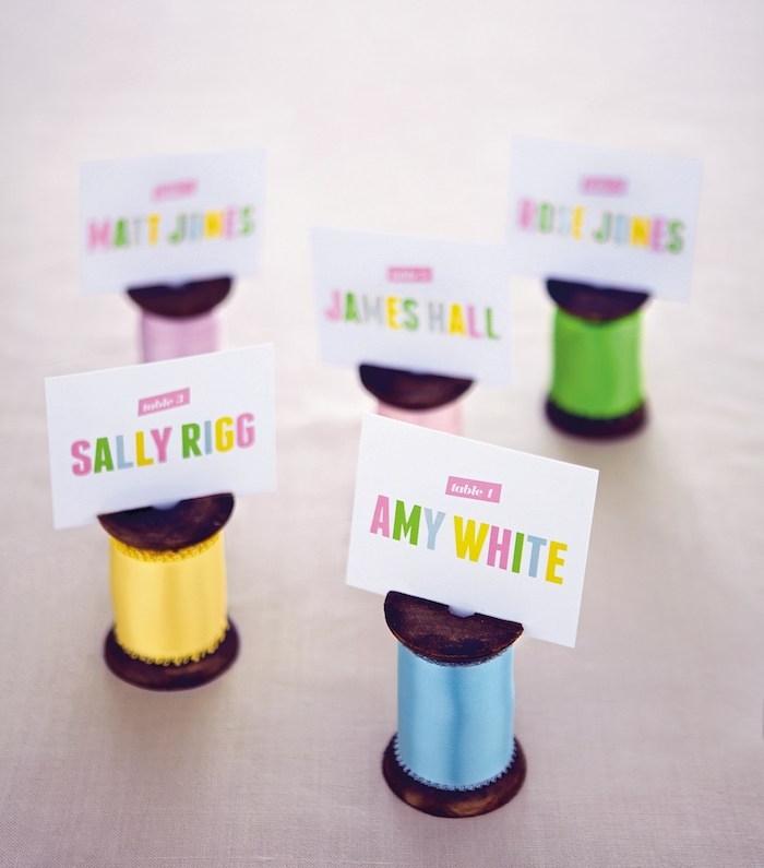 bobine à coudre en bois avec des fils colorés et étiquette avec lettres colorées pour un mariage vintage chic