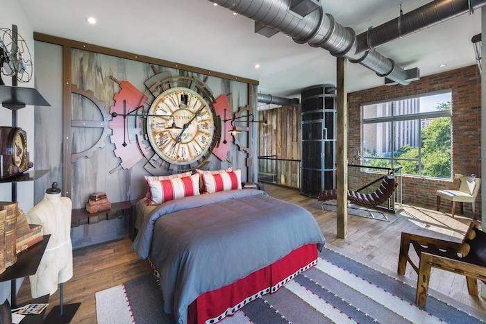 tuyaux apparentes dans une chambre style industriel, linge de lit rouge et gris, mur de briques, horlogerie murale sur mur d accent, parquet bois