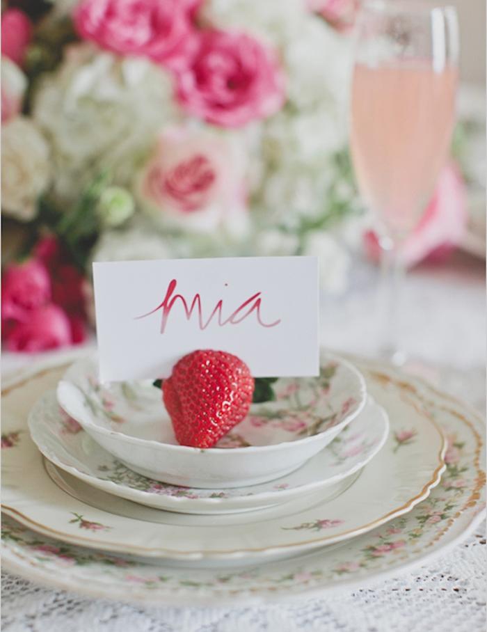 assiettes shabby chic, décorées de motifs floraux avec marque de place fraise et carton blanc avec prénom, centre de table en fleurs