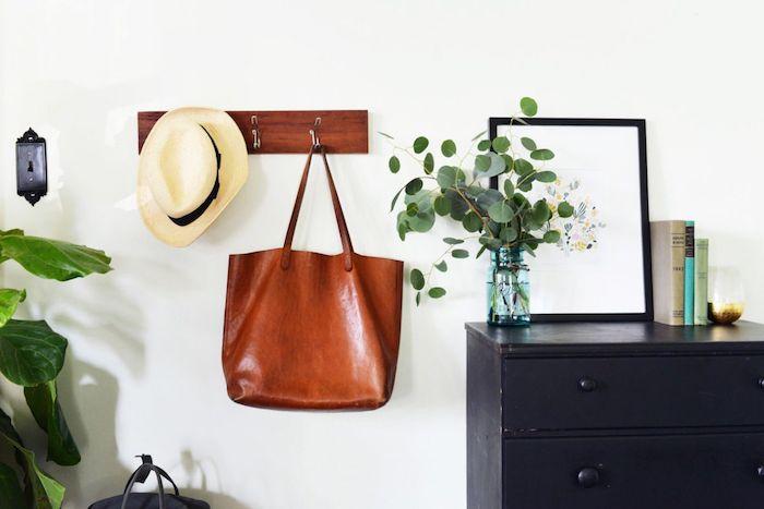 commode en bois repeint de noir, patere en simple planche de bois avec des accroches metalliques, plantes vertes, mur blanc