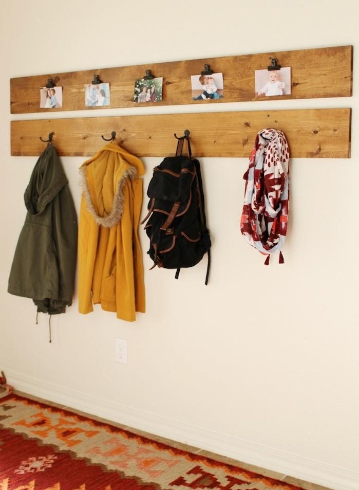 planches de bois clair avec des accroches metalliques, rangement manteaux et accessoires, deco de photos, tapis coloré