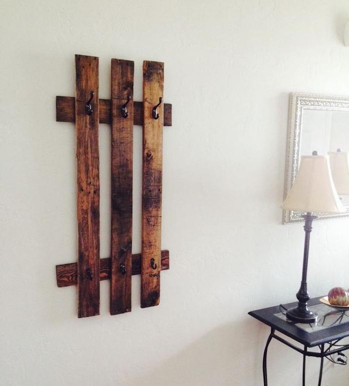 exemple de porte-manteau original en planches de bois brut avec des accroches metalliques noires sur un mur blanc, table basse noire