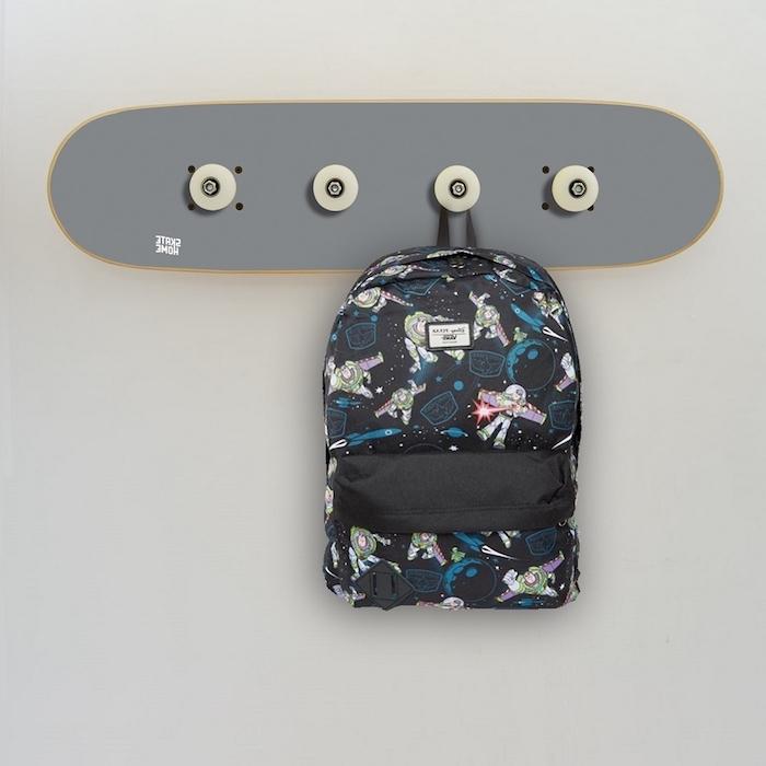 idée de porte manteau mural design en skateboard gris avec des accroches sac à main, mur gris clair