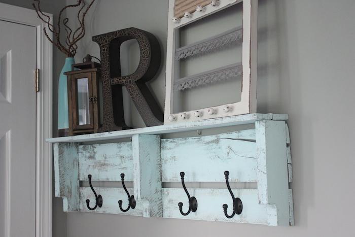 exemple de porte manteau en bois de palette diy avec des accroches noires metalliques, accessoires deco lettre, lanterne, vase, mur gris