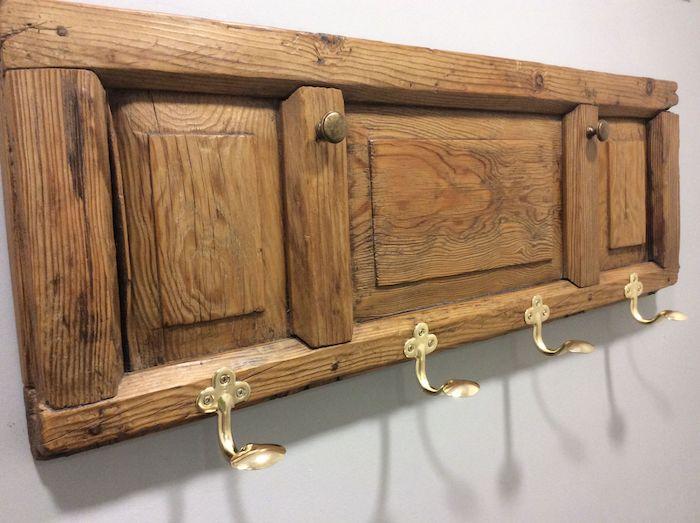 idée de volet de porte placard en bois avec des manches en cuillères dorées pour suspendre manteaux et autres vetements