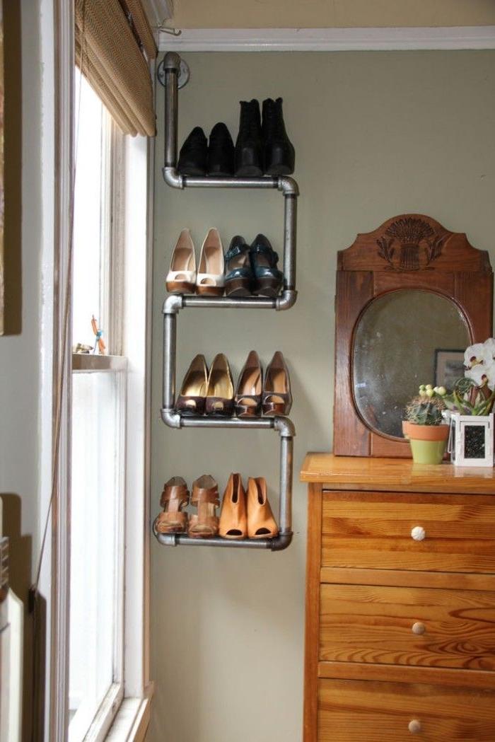 une étagère à chaussure récup à trois niveaux réalisée avec des tuyaux de plomberie, en contraste avec la coiffeuse vintage