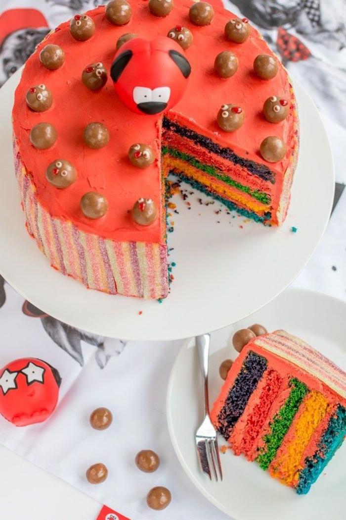 recette de gâteau arc en ciel original recouvert de glaçage rouge et décoré avec des bonbons au chocolat et des rubans acidulés