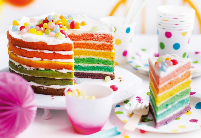 un gâteau arc en ciel traditionnel sans glaçage sur les côtés, nappé de crème chantilly dessus