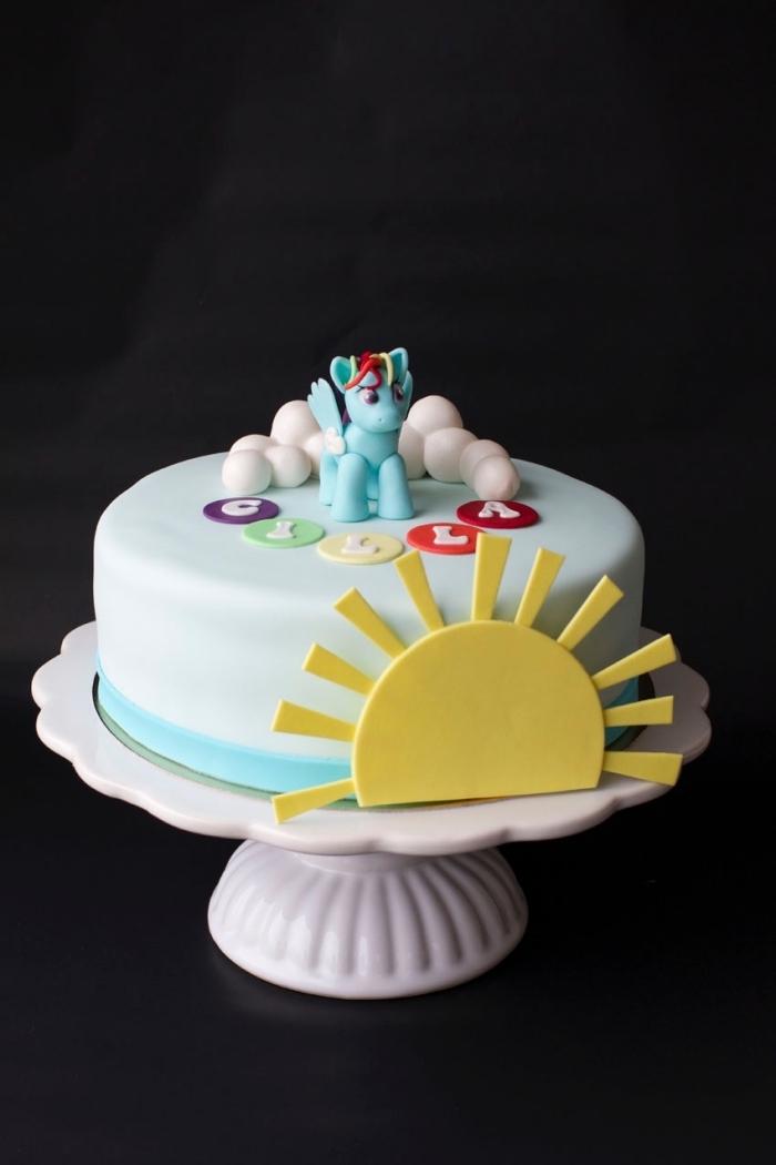 idée de gâteau arc en ciel sur le thème licorne, recouvert de pâte à sucre et décoré avec des modelages en pâte à sucre