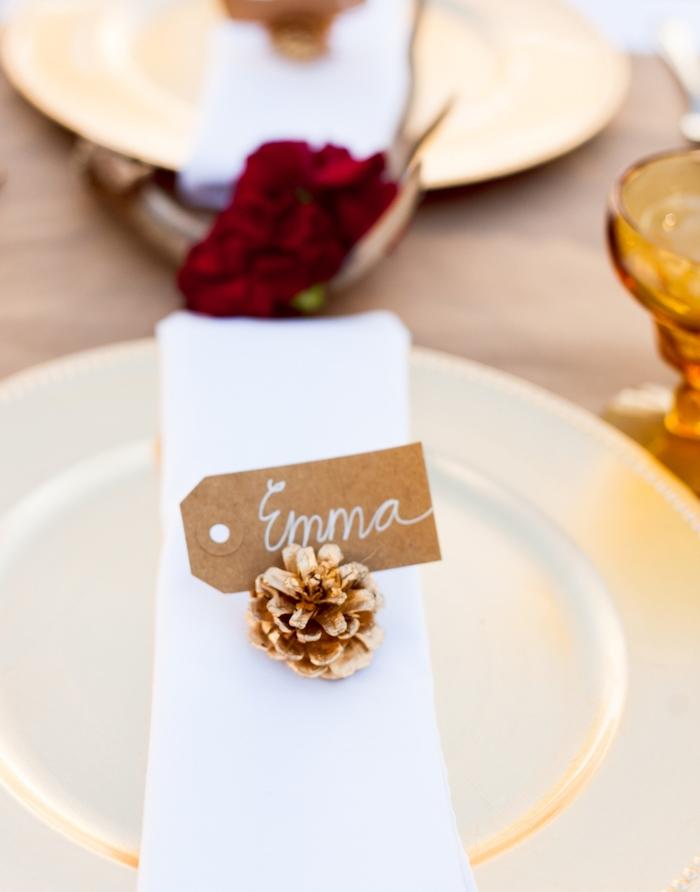 etiquette mariage papier kraft inséré dans une pomme de pin, serviette en tissu blanc, nappe marron et fleur rouge au centre