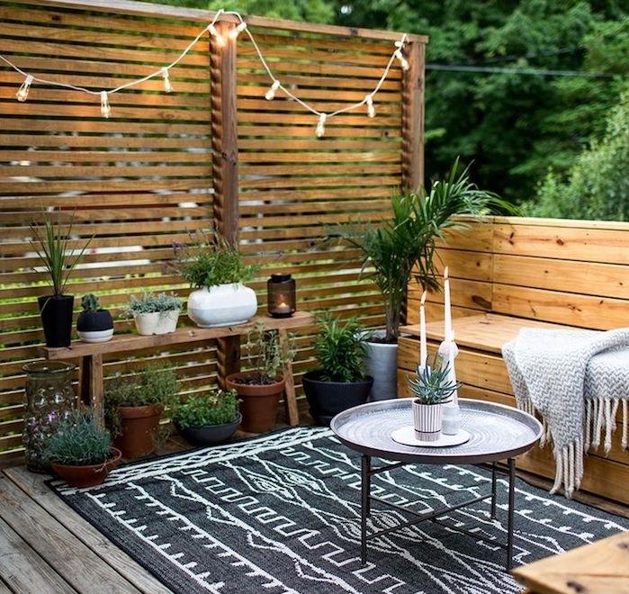 exemple d amenagement terrasse exterieure en banc de bois, tapis noir et blanc, revetement bois, panneau occulant bois, jardiniere palette, guirlande lumineuse, plantes vertes