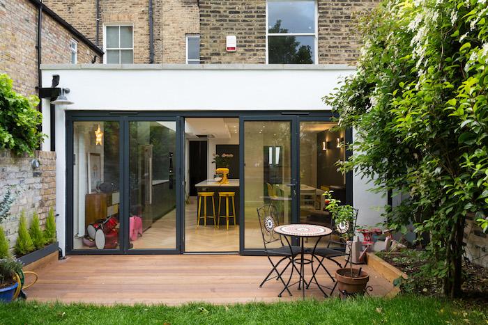 aménagement cour extérieur en terrasse de bois composite, gazon vert, chaises et table métalliques, verrière séparation cuisine extérieur