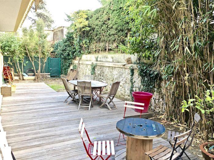 sol en bois brut, table touret et table et chaises bois et métal, bambous plantés, mur de pierre et végétation