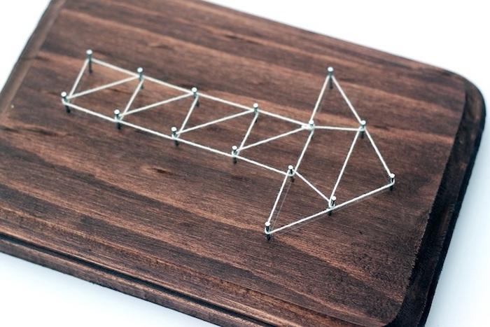 string art flèche sur une tablette en bois marron, clous et fils croisés, activité manuelle fete des peres