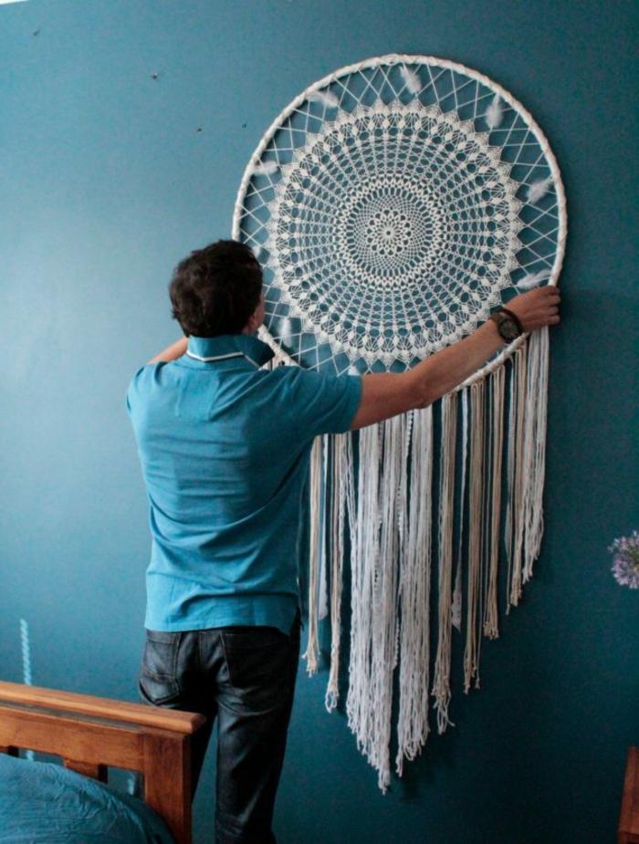 tapis mural avec un attrape-rêve en blanc avec des franges longues, mur peint en bleu canard, chambre adulte, habiller un mur en macramé