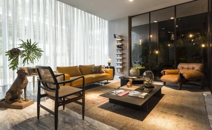 salon en gris et vert, tapis couleur terracota, rideaux blancs, table basse rectangulaire, grand fauteuil marron