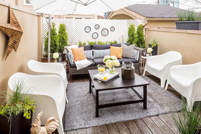 amenagement patio sur une terrasse exterieur avec canapé décoré de coussins, chaises blanches, tapis gris sur un sol en bois, quelques plantes en pots