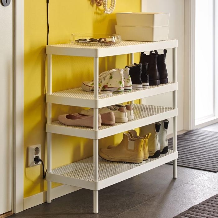 une jolie etagere chaussure blanche en métal perforé à quatre niveau en joli contraste avec le mur jaune