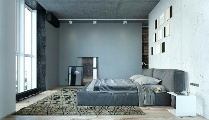 mur gris paon dans une chambre, éclairage industriel, tapis marron, lit plateforme