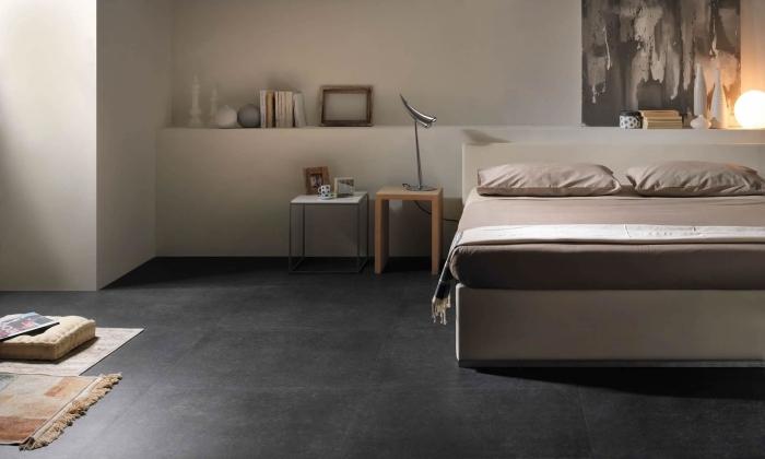 chambre à coucher large aux murs blancs avec sol gris anthracite, objets décoratifs à finition bois pour une ambiance cozy