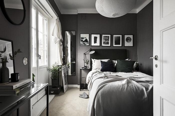 design intérieur dans une chambre à coucher aux murs gris anthracite avec plafond et portes blanches, déco en blanc et noir