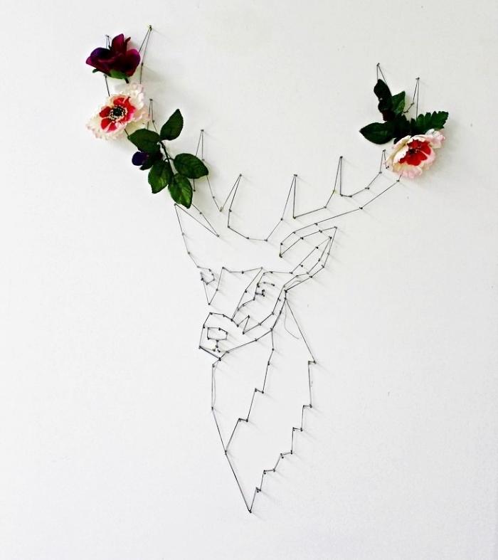 décoration murale de style minimaliste faite avec un gabarit fil tendu à design cerf blanc et noir avec cornes en fleurs
