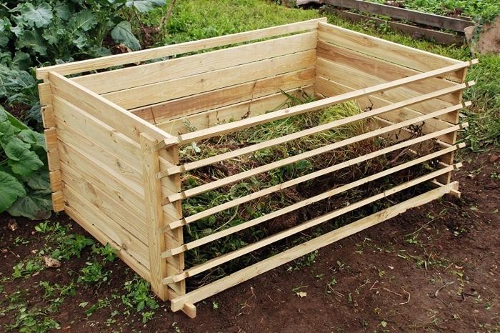 exemple de petit composteur fait main à partir de bois avec mécanisme d'ouverture et aération installé dans le jardin