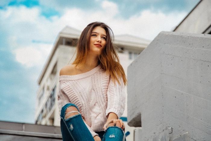 comment bien s'habiller avec une paire de jeans déchirés et un pull rose pastel, cheveux longs de couleur châtain foncé aux pointes éclaircies